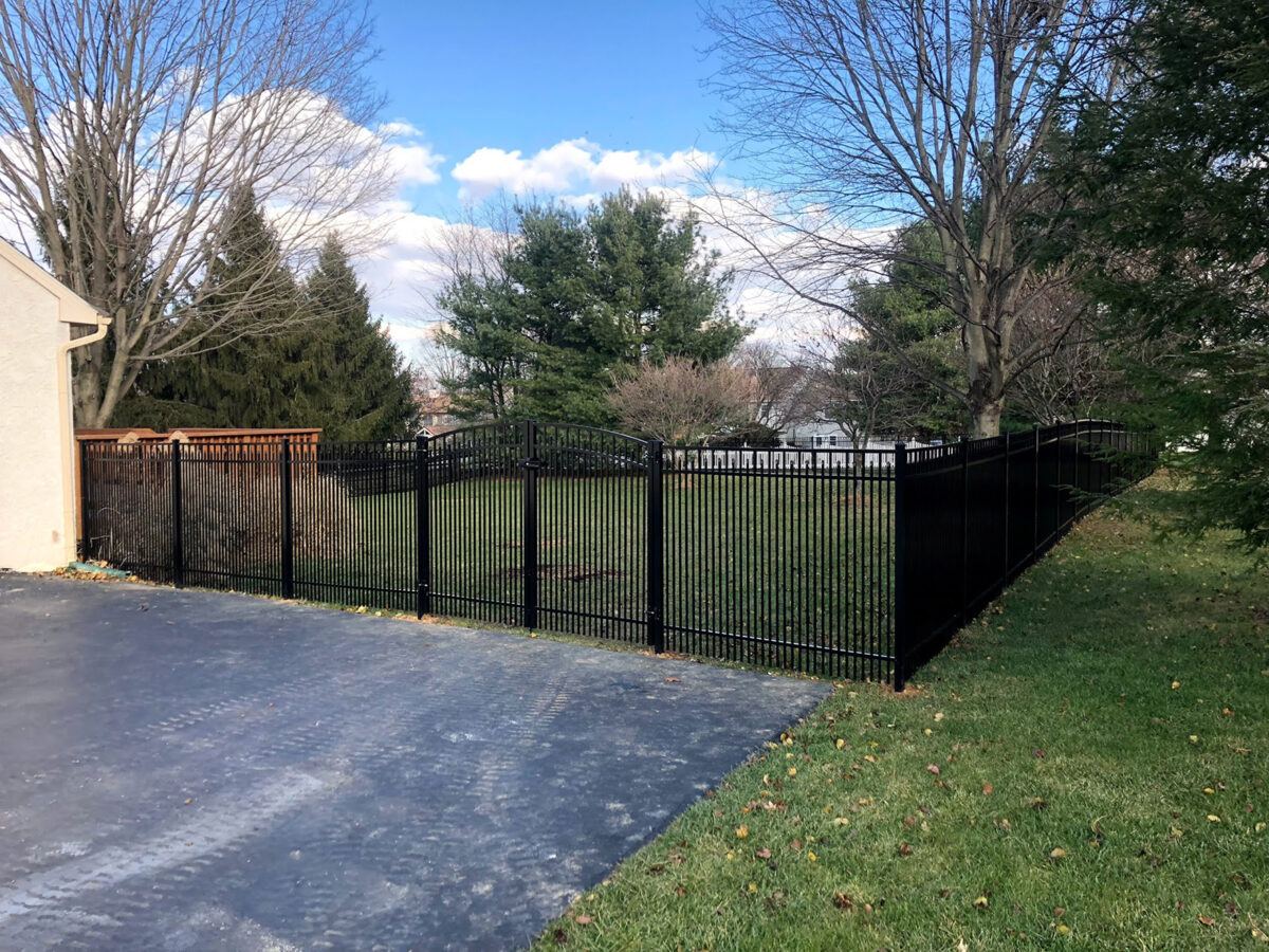 Ornamental aluminum fence with arched double gate in yard