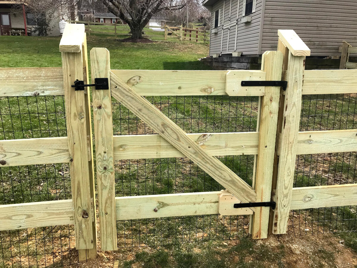 rail fence with wire mesh in yard with gate