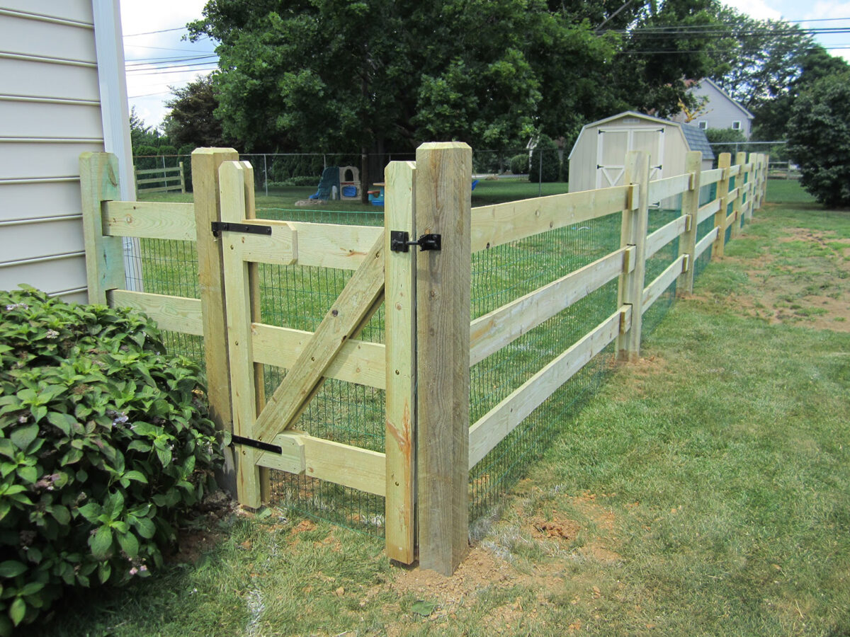 slip rail fence with wire mesh in yard with gate