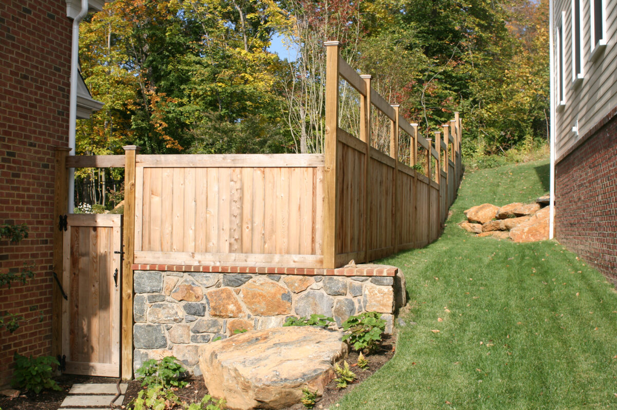 wooden fence with small gate on to pof wall