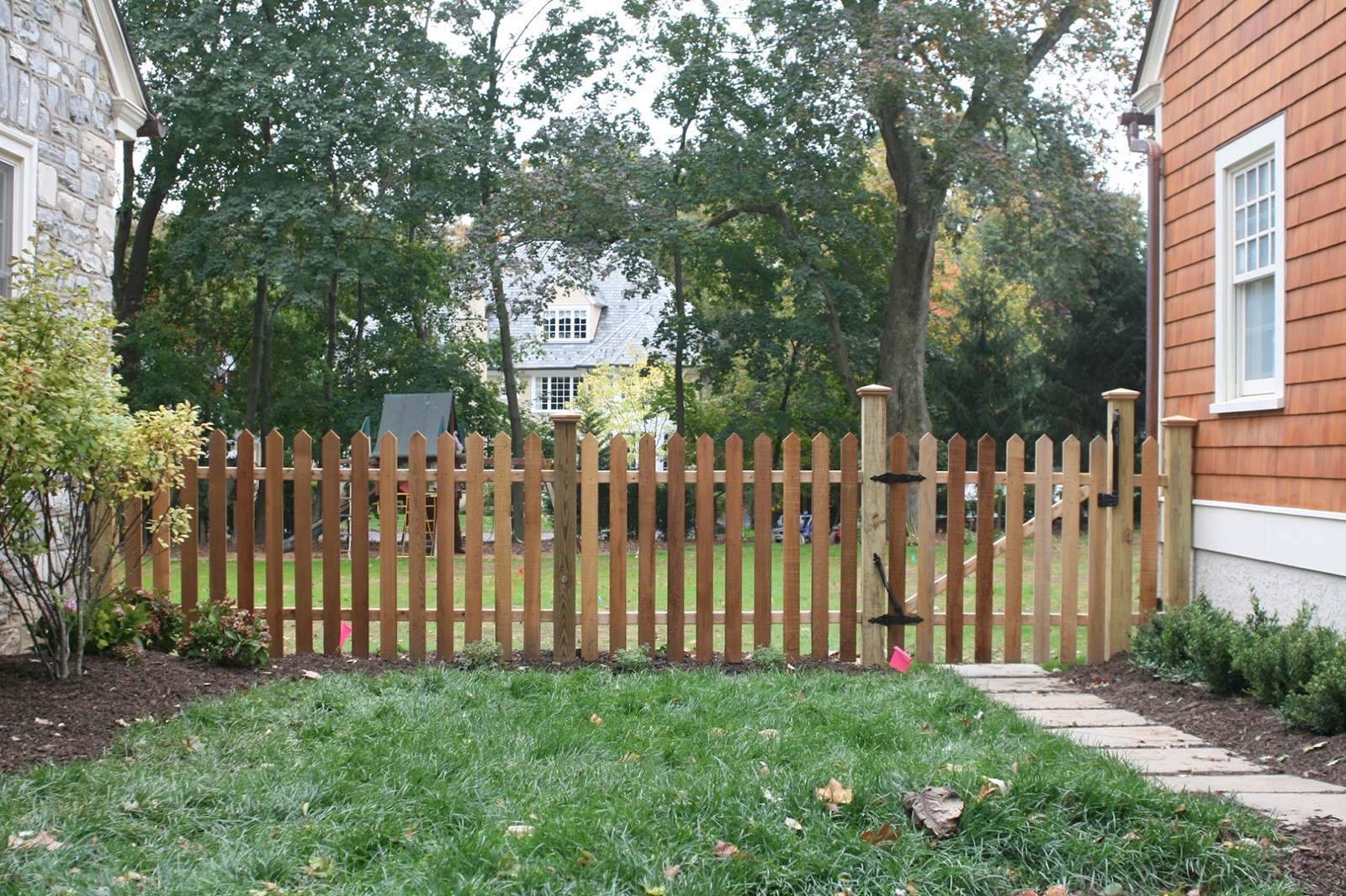 wood picket fence with post caps and self closing gate