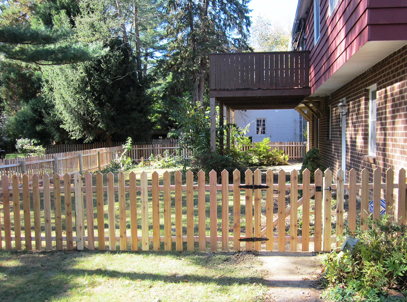 wood picket fence with gate around yard