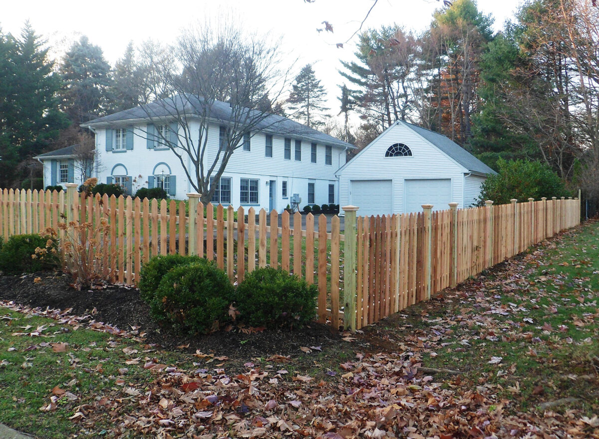wood picket fence with post caps around yard