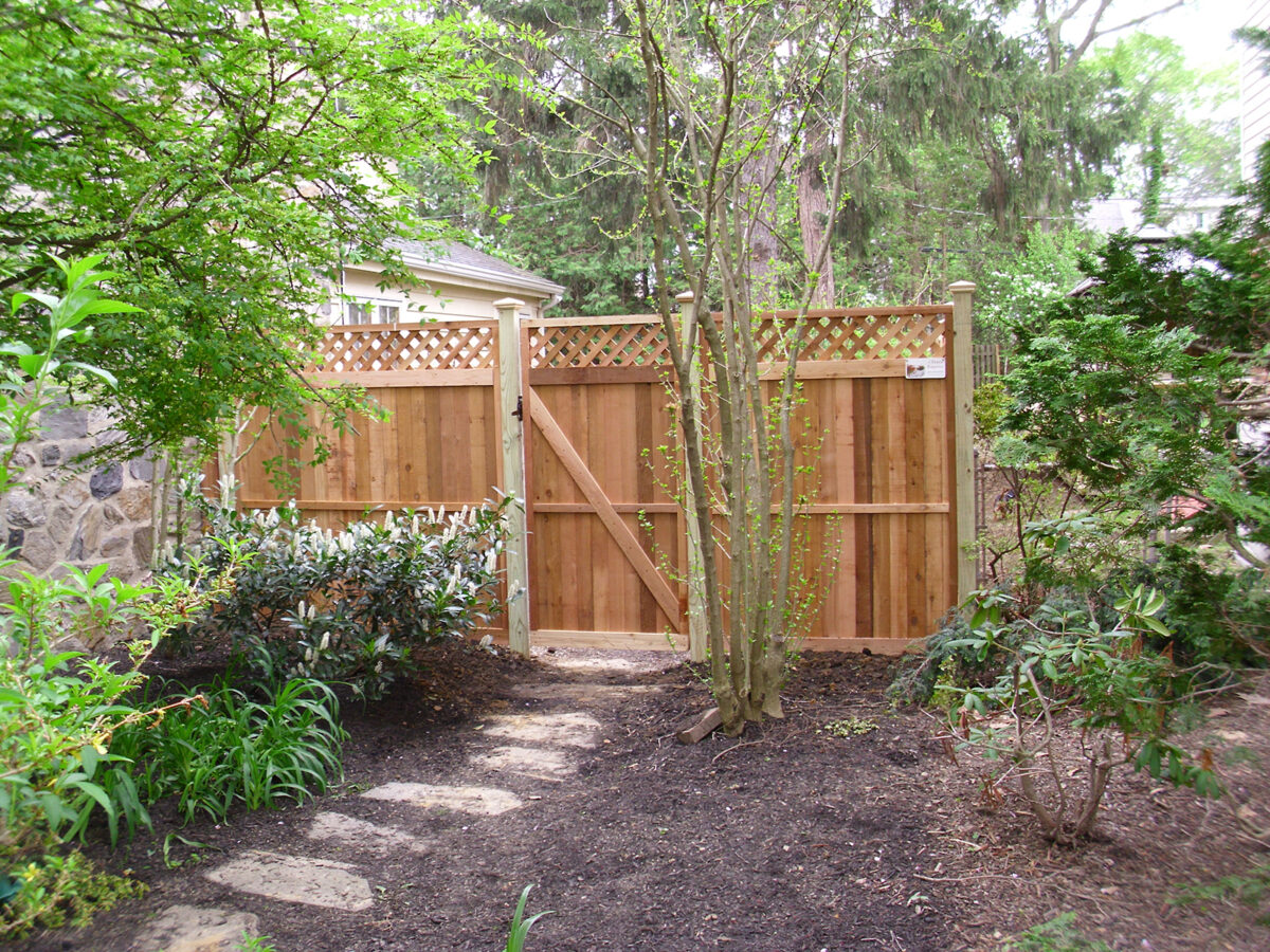 Framed wood privacy fencing with lattice in back yard with gate