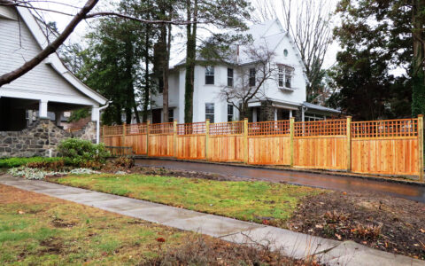 Framed wood privacy fencing with lattice beside drive