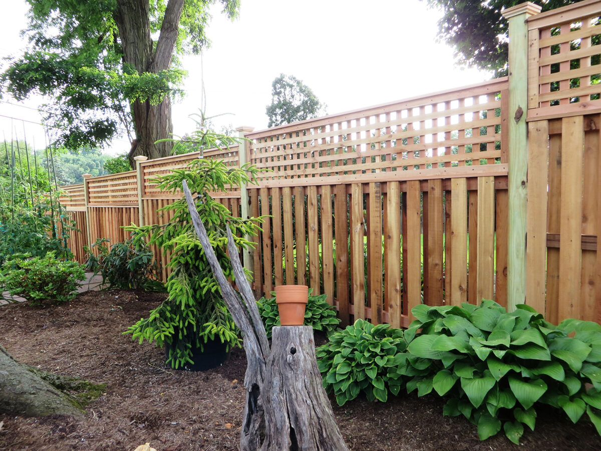 Framed wood privacy fencing with lattice in back yard