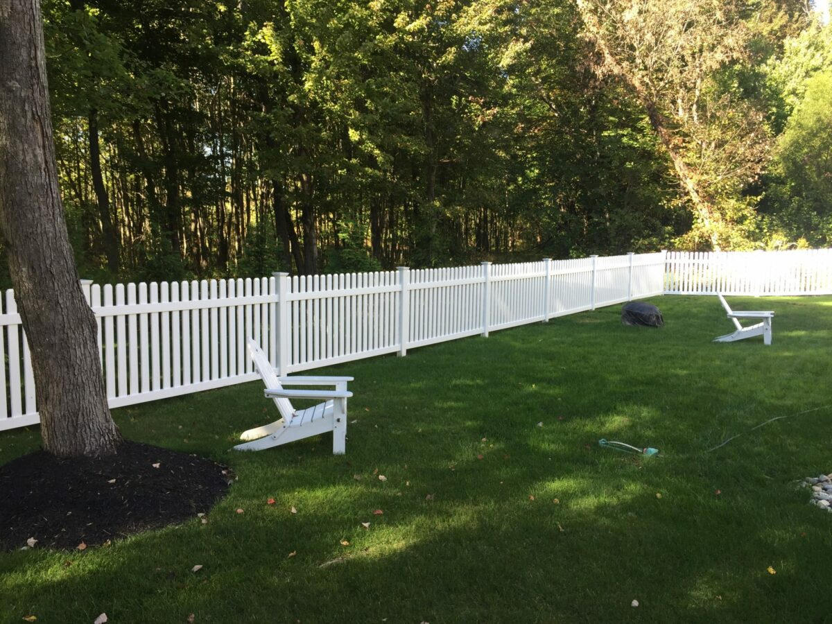white vinyl picket fence in yard with a chair
