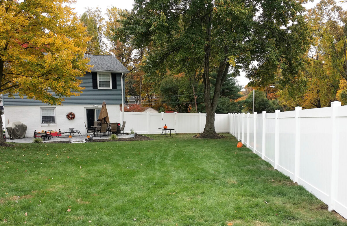 white vinyl privacy fence in backyard