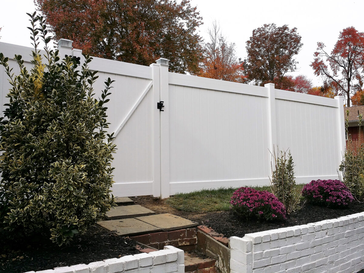 white vinyl privacy fence with gate and solar post caps