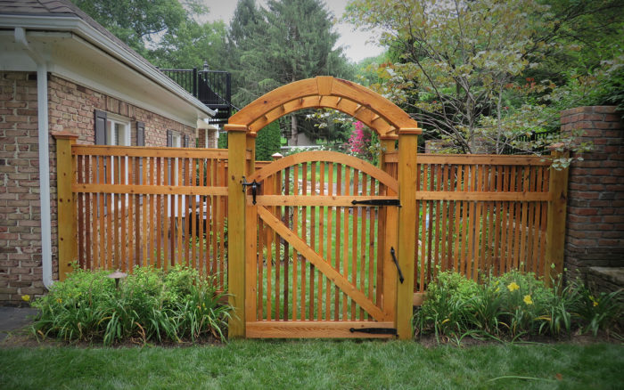 wooden semi-private fence with arched gate and arbor