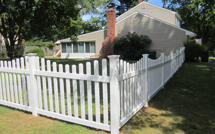 white vinyl concaved picket fence with post caps in yard