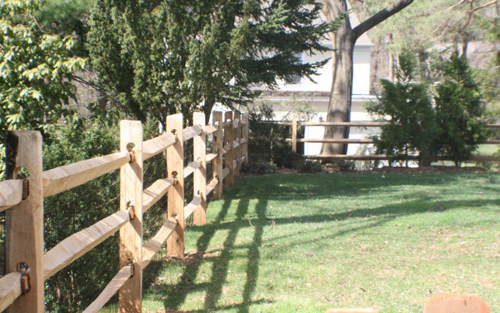 3-rail split-rail fence with wire mesh to protect pets in yard