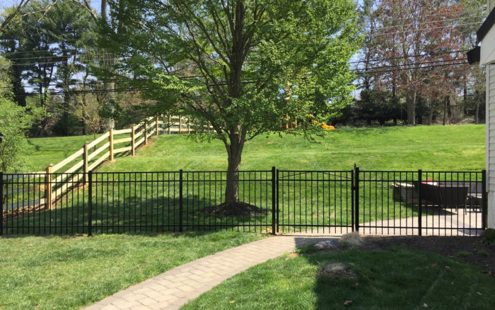 Black metal fence and wooden rail fence on sloping lawn