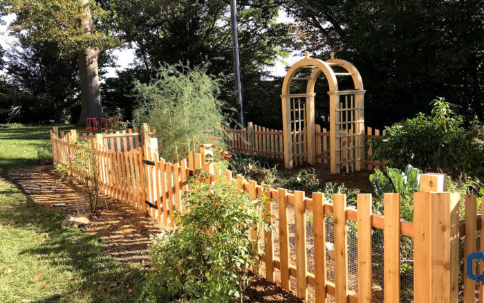 red cedar picket fence around garden with arbor