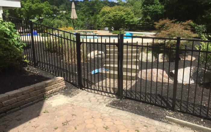 black ornamental fence around pool with gate