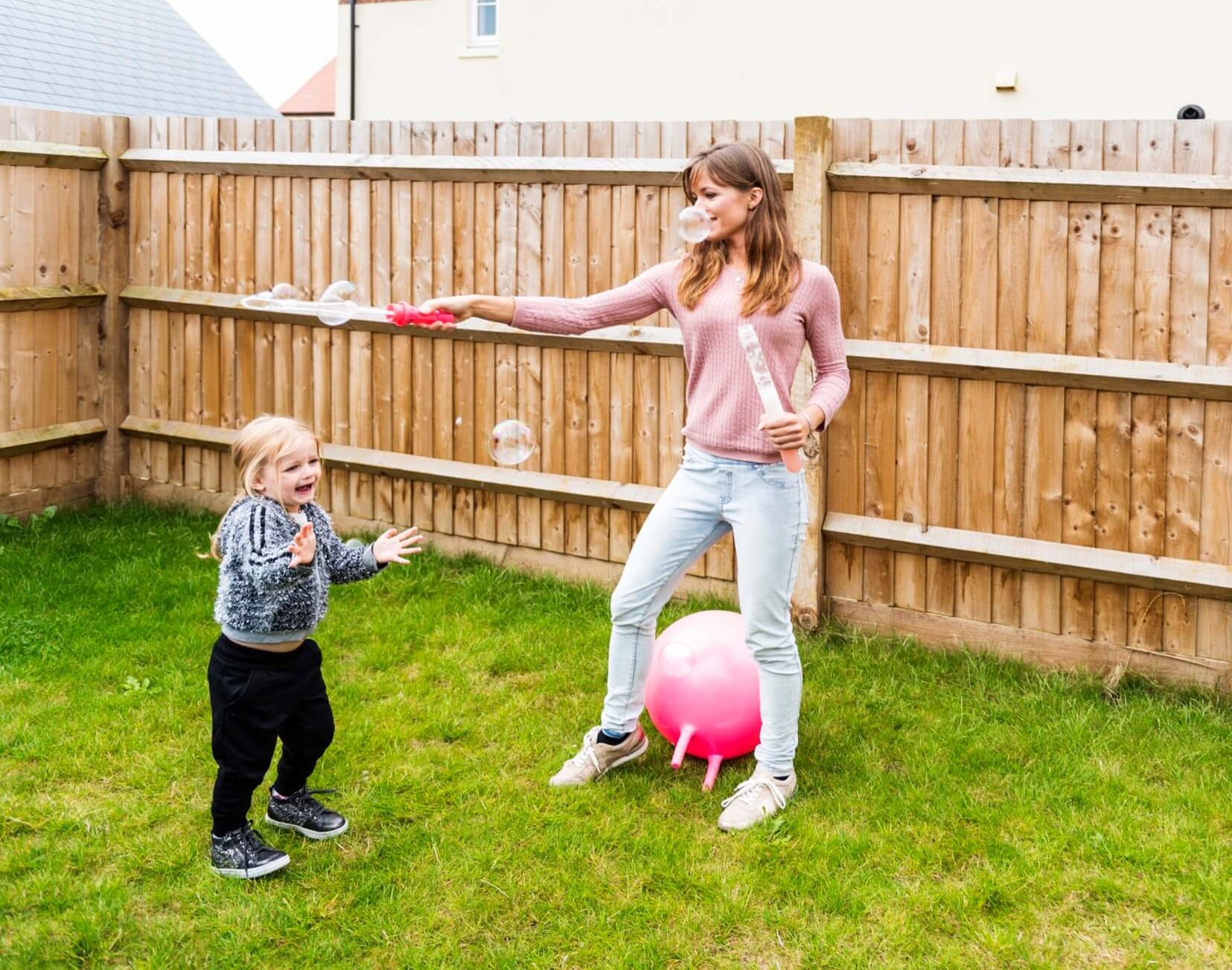 Parent and child playing in fenced yard