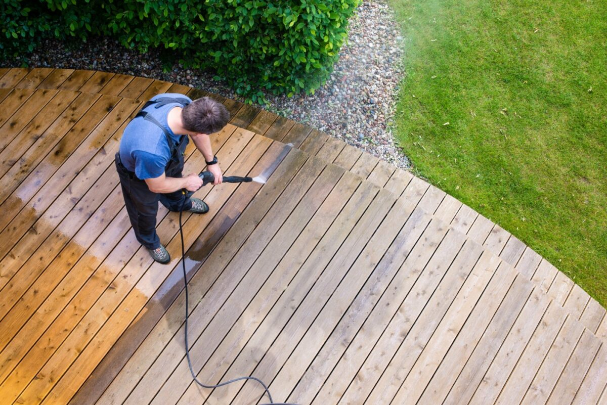 Professional power washer cleaning a wooden deck